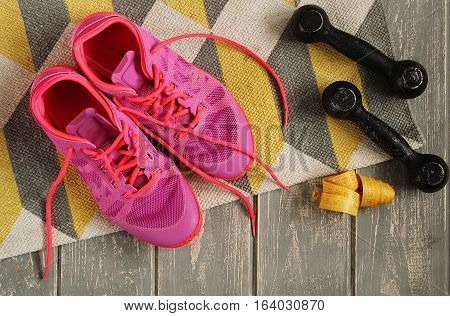 Trainers, dumbbells, ribbon, mat on floor. Stock photo Sporty mock up
