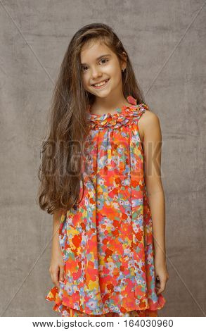 teen girl with loose hairstanding in bright summer dress smiling.with long hair