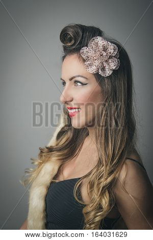 Side portrait of smiling fashionable woman with fancy hairstyle and bow in hair studio background
