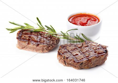 Steak well done served with saucedecorated with sprig of rosemary and spices