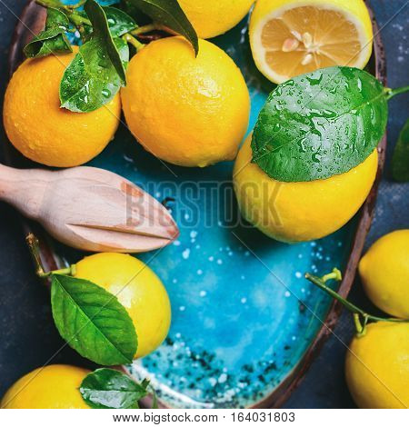 Close-up of freshly picked wet lemons with leaves in bright blue ceramic plate, top view, square crop, copy space
