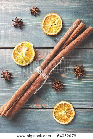 Dried orange anise and cinnamon sticks on green wooden table. Toned photo.