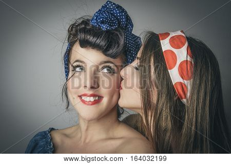 Portrait of two happy young women in retro clothes one kissing the cheek of her friend studio background