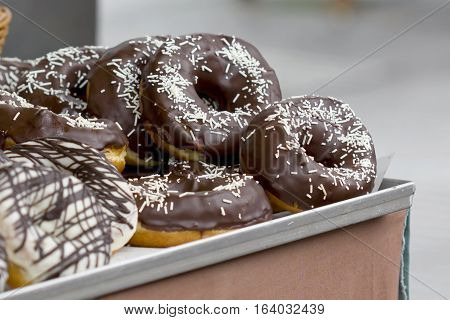 Closeup image of big chocolate donuts on a tray.