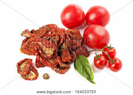 Sun dried tomatoes with basil and ripe tomatoes isolated on white.