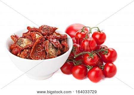 Sun dried tomatoes and ripe tomatoes isolated on white.