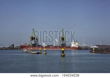 coal industry in the harbor of rotterdam netherlands. Vessel loading coal