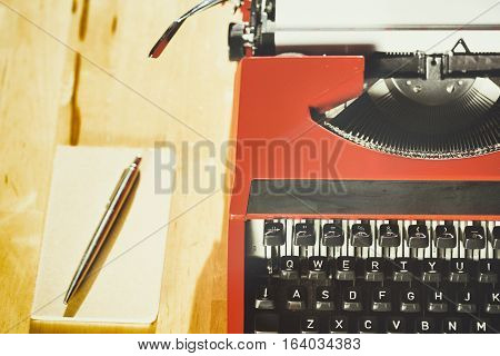 Top view of an 80s typewriter with a paper notebook next to it. Shallow DOF focus on the keys.