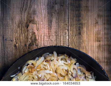 Fried onion in a frying pan. Blank space. View from above