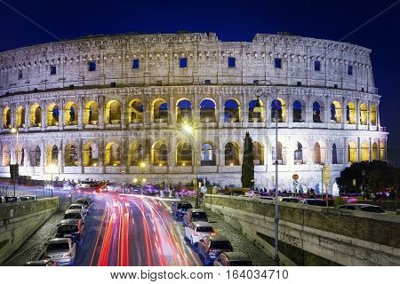 Long exposure to Colosseum taken at night with the shining path of cars. Front view of the Colosseum facade.