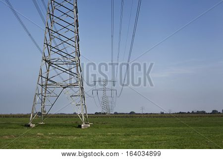 High voltage electrical transmission towers electricity pylons and power lines on green field