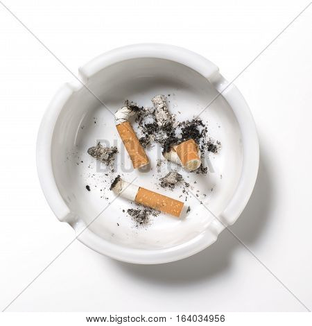 Overhead of old cigarettes in a ashtray on white background