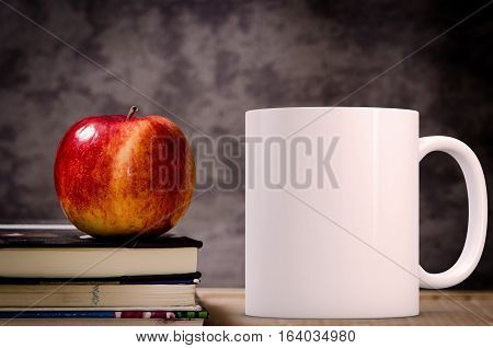 Mockup Styled Stock Product Image white mug that you can add your custom design/quote to. Mug is next to books with an apple on them.