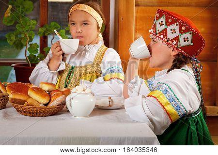 Two girls drink tea, spun yarn, embroider, chatting and having fun.