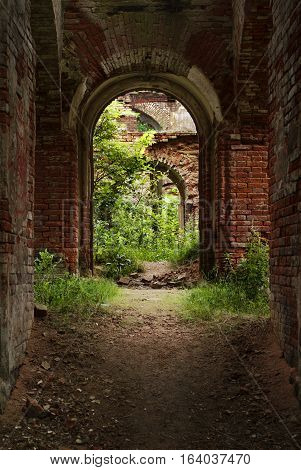 Arch in destroyed brick house in the summer