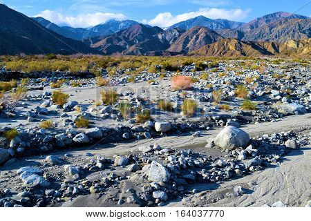 Dry rocky and sandy flood wash with mountains beyond taken on the desert floor in Whitewater, CA