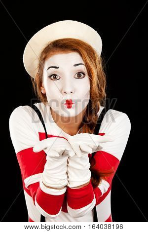 Portrait of the female MIM comedian blows a kiss isolated on black background