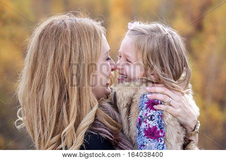 Mother and daughter playing nose to nose in autumn nature