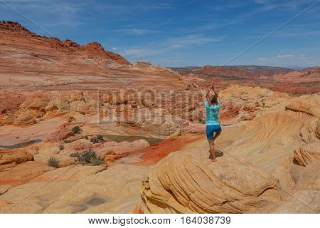 Doing yoga in the red deserto of The Wave, Coyote Buttes Paria Canyon-Vermilion Cliffs Wilderness, Utah