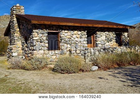 Historic stone cabin in the rural desert surrounded by sage plants taken at Mission Creek Preserve near Palm Springs, CA
