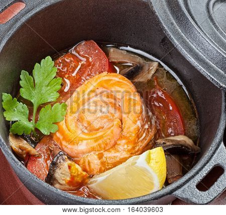 Stewed salmon with vegetables and lemon in a pan.