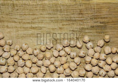 Top view of chickpeas (chick peas Cicer arietinum Bengal gram garbanzo bean ceci or Kabuli Chana vegetables) on natural wooden bacgkround
