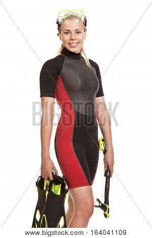 Young smiling blond woman in a wet suit for swimming poses holding flippers and snorkel.Studio short. Isolated on white background.