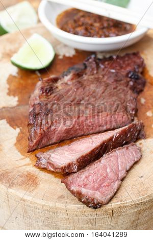 Beef steak on wood background.Northeastern Thai Style Grilled Beef with