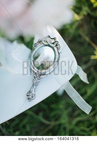 charges of the bride outdoors. vintage silver pocket mirror close up.