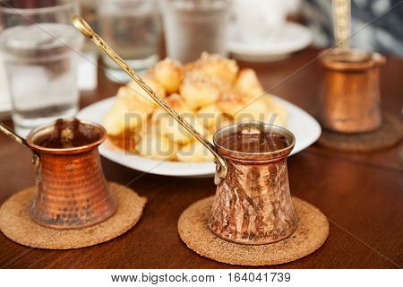 Coffee served in three pots with three cups of water and traditional southern sweets. Small DOF.
