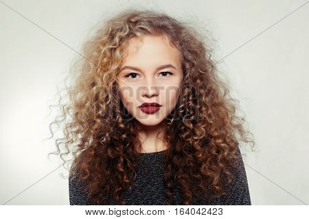 people youth and beauty concept - Beauty young woman with curly big and long hair. Permed hair. Glamour lady Beauty Girl on grey background. Beautiful Woman Portrait. Blond Wavy Hair
