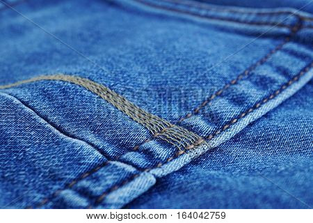 Macro detail of a yellow thread stitching typical blue men's jeans