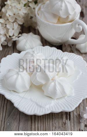 Mini meringue on white porcelain, on white table. Natural light, selective focus.