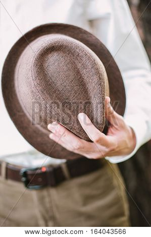 the man holds a trilby hat in hand. brown men's trilby hat close up. groom and his trilby hat.