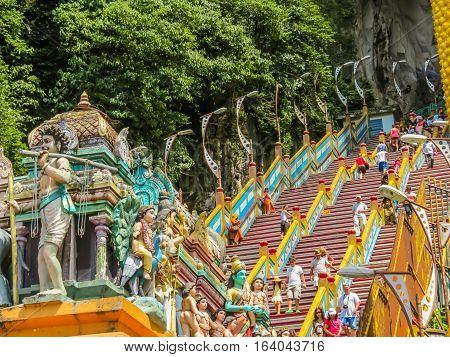 KUALA LUMPUR, MALAYSIA - JANUARY 13, 2014: Pilgrims and visitors go on the huge ladder to Batu Caves. Kuala Lumpur, Malaysia