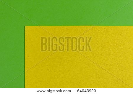 Eva foam ethylene vinyl acetate sponge plush lemon yellow surface on apple green smooth background