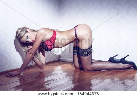 Sexy blonde woman in black underwear kneeling on floor sensuality