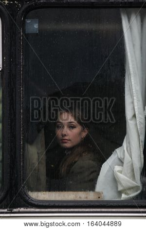 BUCHAREST ROMANIA - DECEMBER 1 2010: A military woman is seen behind a bus window during a military parade. More than 3000 soldiers and personnel from security agencies take part in the massive parades on National Day of Romania.