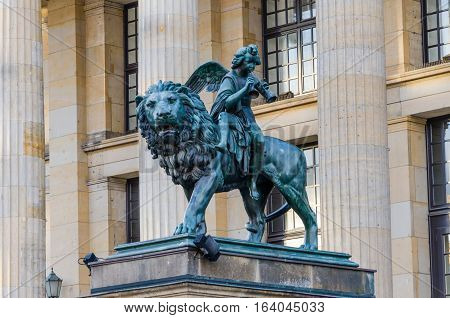 Closeup of lion and angel sculpture in front of Konzerthaus at Gendarmenmarkt square, Berlin, Germany.