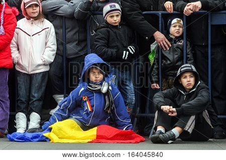 BUCHAREST ROMANIA - DECEMBER 1 2009: Children are watching the military parade on National Day of Romania. More than 3000 soldiers and personnel from security agencies take part in the massive parades on National Day of Romania.