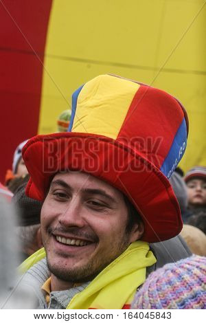 BUCHAREST ROMANIA - DECEMBER 1 2009: A man wearing a hat with Romanian national flag colors is taking part to a military parade on National Day of Romania. More than 3000 soldiers and personnel from security agencies take part in the massive parades on Na