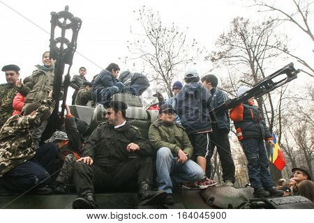 BUCHAREST ROMANIA - DECEMBER 1 2009: Children are playing on a tank during a military parade on National Day of Romania. More than 3000 soldiers and personnel from security agencies take part in the massive parades on National Day of Romania.