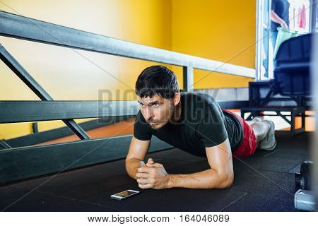Fitness man doing exercise strap - Plank standing on his elbows at the gym. It notes the time on the phone.