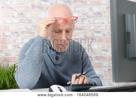 mature businessman having eyesight problems he is using calculator