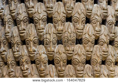 Pattern of many wood carved heads on chair at traditional Fon's palace in Bafut, Cameroon, Africa.