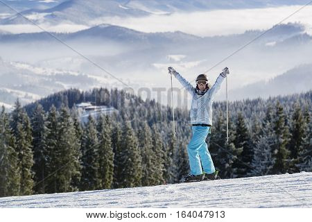 Young women on ski smiling on the background of mountain winter resort
