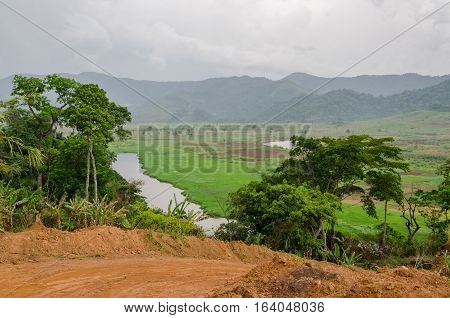River and dirt road with mountains and lush vegetation at Ring Road in Cameroon, Africa.