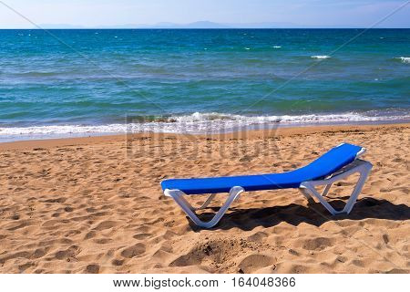 one sunbed for suntan is located a closeup on the sandy seashore and the horizon in a distance