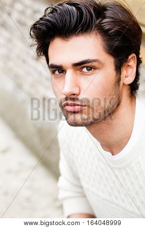 Handsome beautiful young man outdoor. Fashion hairstyle. Handsome young boy looking. Stylish hair, charming and attractive look. Slight beard and white sweater. Outdoors in the city. Clear and bright environment.
