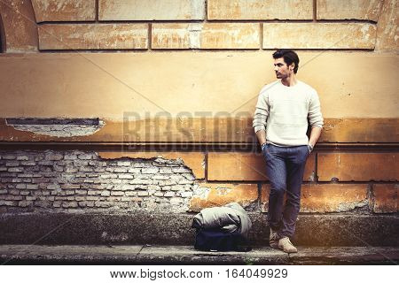 Street fashion model tourist man outdoor. Waiting on grunge wall. A beautiful model man waiting leaning against an old wall. Vintage scene, old ruined wall. On the ground theres his bag and coat. The boy wears a white sweater and gray trousers.